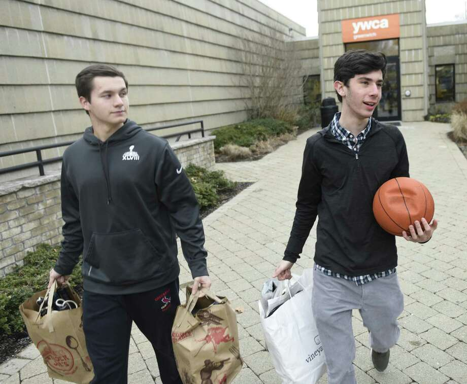 GHS junior Charlie Povinelli, left, and YES Club co-president Greg Goldstein collect used sports equipment from a collection point at the YWCA in Greenwich, Conn. Wednesday, Feb. 1, 2017. Greenwich High School's YES (Youth Equipment Sharing) Club collected 1,500 pieces of lightly-used sporting goods for less-fortunate children last year and hopes to top 2,500 this year in their annual winter drive. Photo: Tyler Sizemore / Hearst Connecticut Media / Greenwich Time