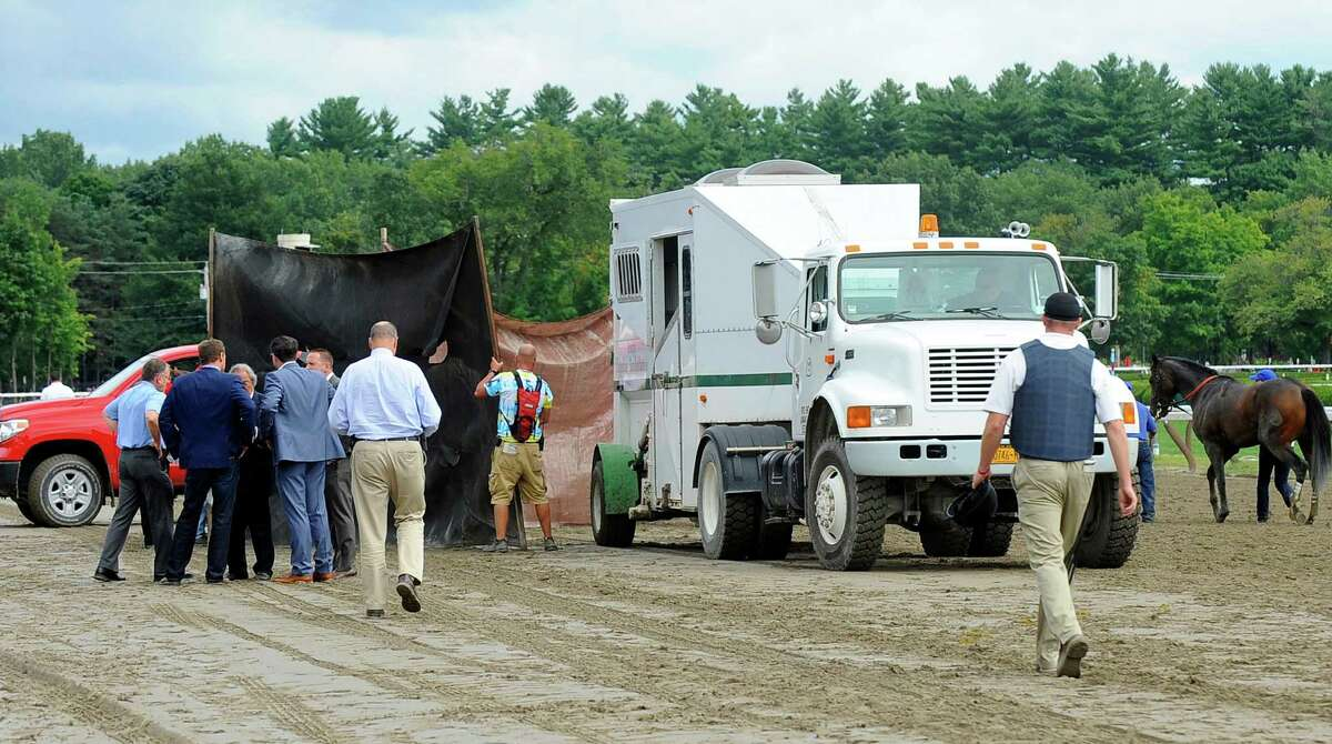 Ludicrous is shielded from spectators before being taken away in a equine ambulance after getting injured coming down the stretch during the fourth race prior to the running of the Travers Stakes horse race at Saratoga Race Course in Saratoga Springs, N.Y., Saturday, Aug. 23, 2014. (AP Photo /Hans Pennink)