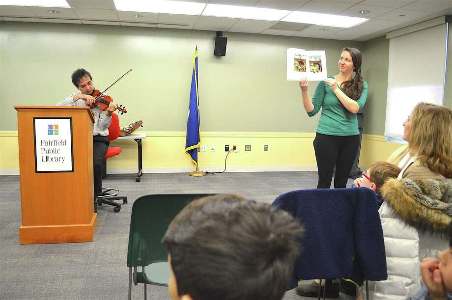 """Musician Yaroslav Kargin adds live music to a reading of the kids' book """"Mole Music,"""" aided by Caitlin Daly, at a """"Creating Musical Readers"""" program, featuring an Instrument Discovery Zone, run by the New Haven Orchestra at Fairfield Public Library, Saturday, Feb. 4, 2017, in Fairfield, Conn. Photo: Jarret Liotta / For Hearst Connecticut Media / Fairfield Citizen News Freelance"""