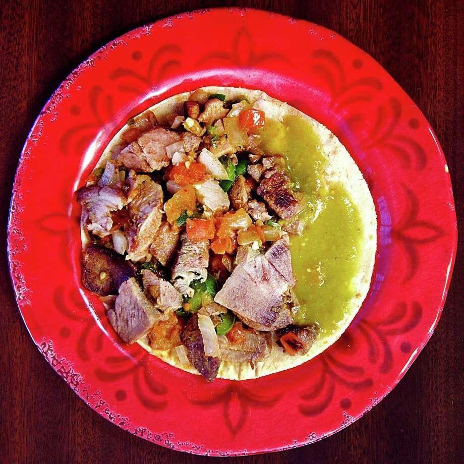 Carnitas a la Mexicana taco on a handmade corn tortilla from Taquería Cazadores. Photo: Mike Sutter /San Antonio Express-News