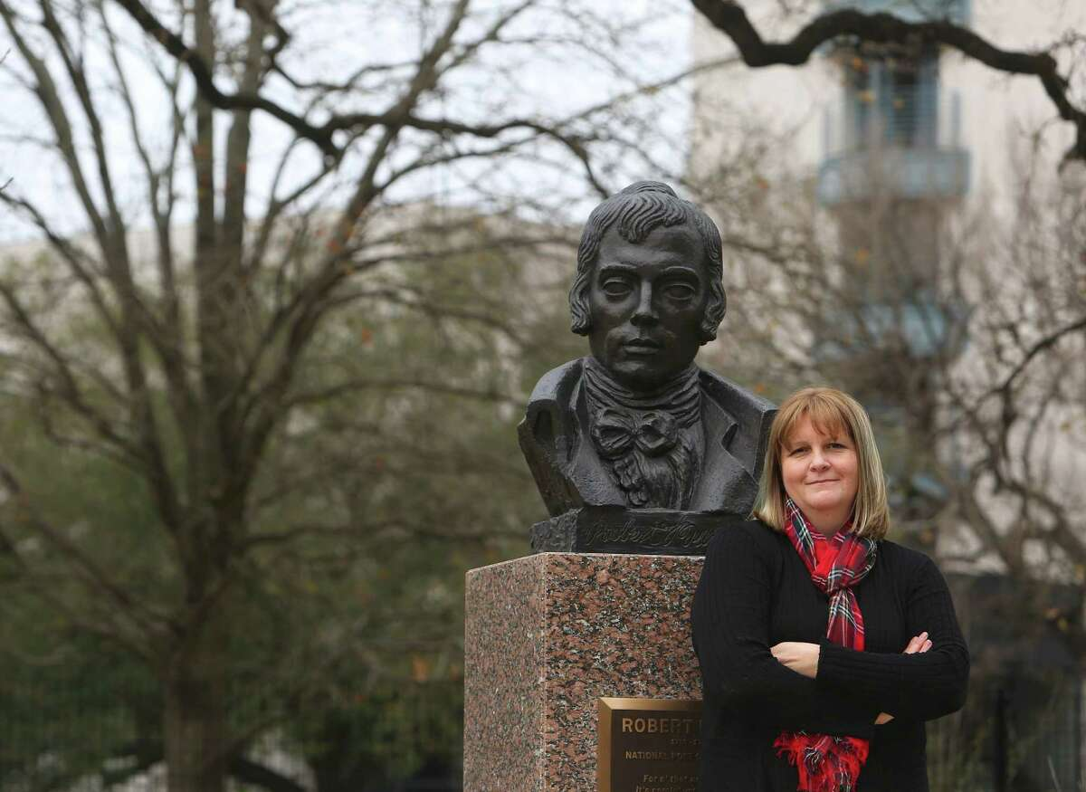 """Writer Caroline Leech stands next to a bust of Scottish poet Robert Burns on Friday, Feb. 3, 2017, in Houston. Leech, who's from Scotland, is debuting her first novel this week, a Young Adult book entitled """"Wait for Me."""" The book is set during World War II and is about a Scottish girl who falls in love with the German POW assigned to work on her family's farm. (Annie Mulligan / Freelance)"""