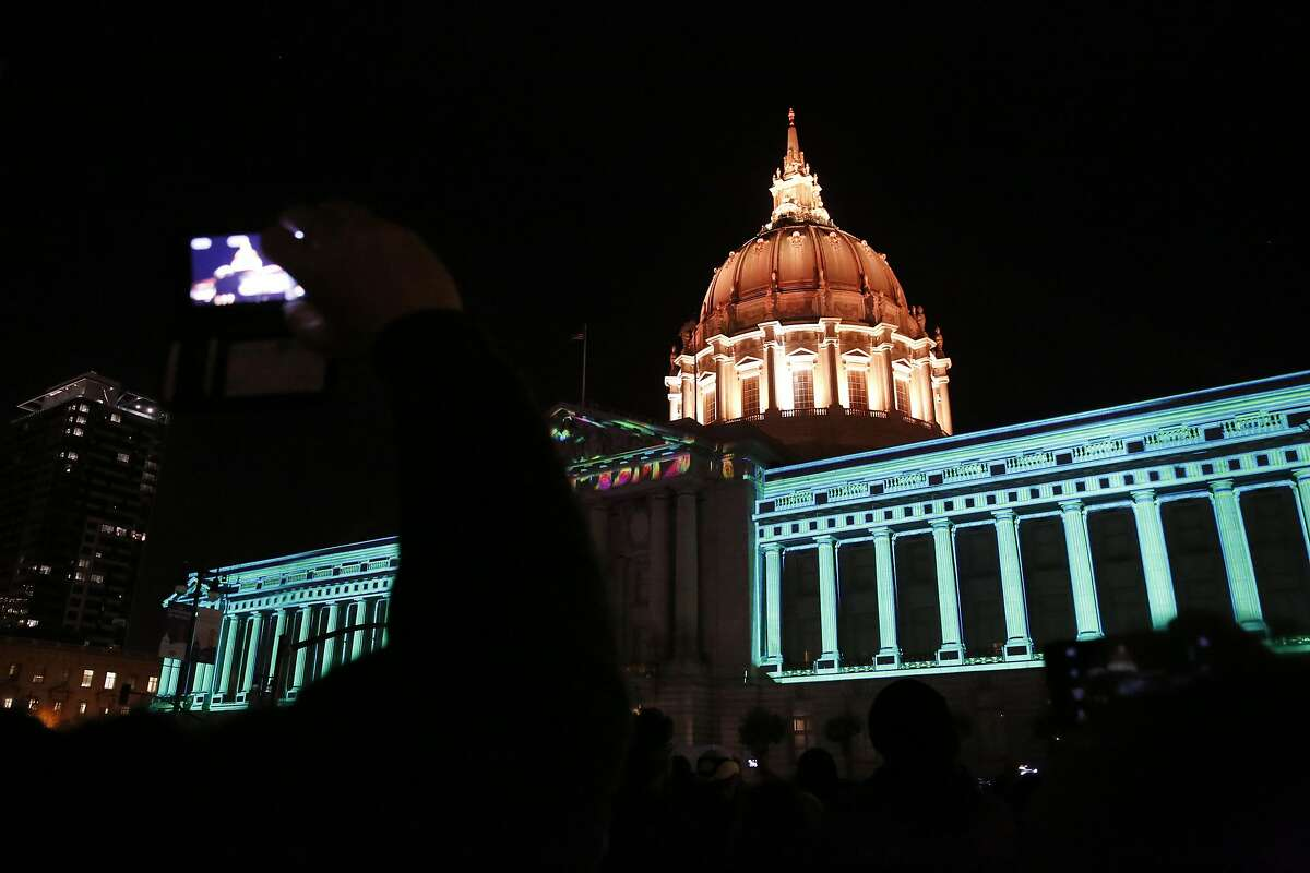 People record the light show on City Hall with their phones during the City Hall Centennial Celebration at Civic Center Plaza June 19, 2015 in San Francisco, Calif.
