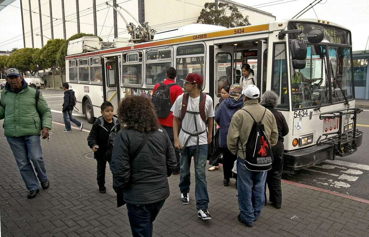 MUNI riders transfer at the bus stop on the corner of Fillmore and Geary Streets in San Francisco.