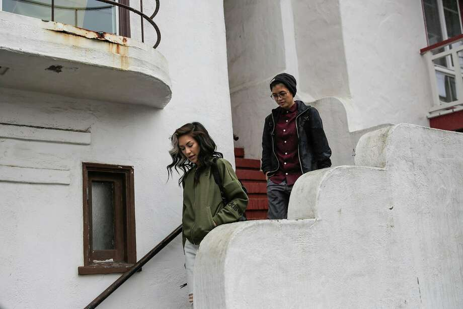 (l-r) Chloe Rainwater and friend Dom DeGuzman walk down the stairs as they leave Dom's house to go out to lunch in San Francisco, California, on Monday, Feb. 6, 2017. Chloe and Dom, who have known each other since high school and dated on and off  throughout the years, reconnected recently through a lesbian dating app called Her. Photo: Gabrielle Lurie, The Chronicle