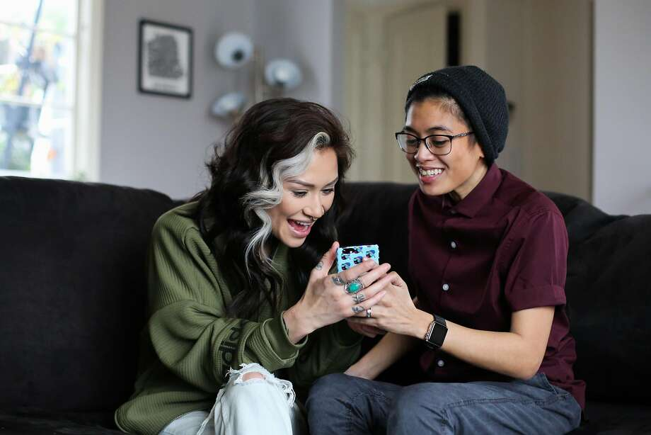 Chloe Rainwater (left) and Dom DeGuzman laugh as they check out something on DeGuzman's phone in San Francisco. Photo: Gabrielle Lurie, The Chronicle