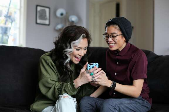 (l-r) Chloe Rainwater and friend Dom DeGuzman laugh as they check out something on Dom's phone in San Francisco, California, on Monday, Feb. 6, 2017. Chloe and Dom, who have known each other since high school and dated on and off  throughout the years, reconnected recently through a lesbian dating app called Her.
