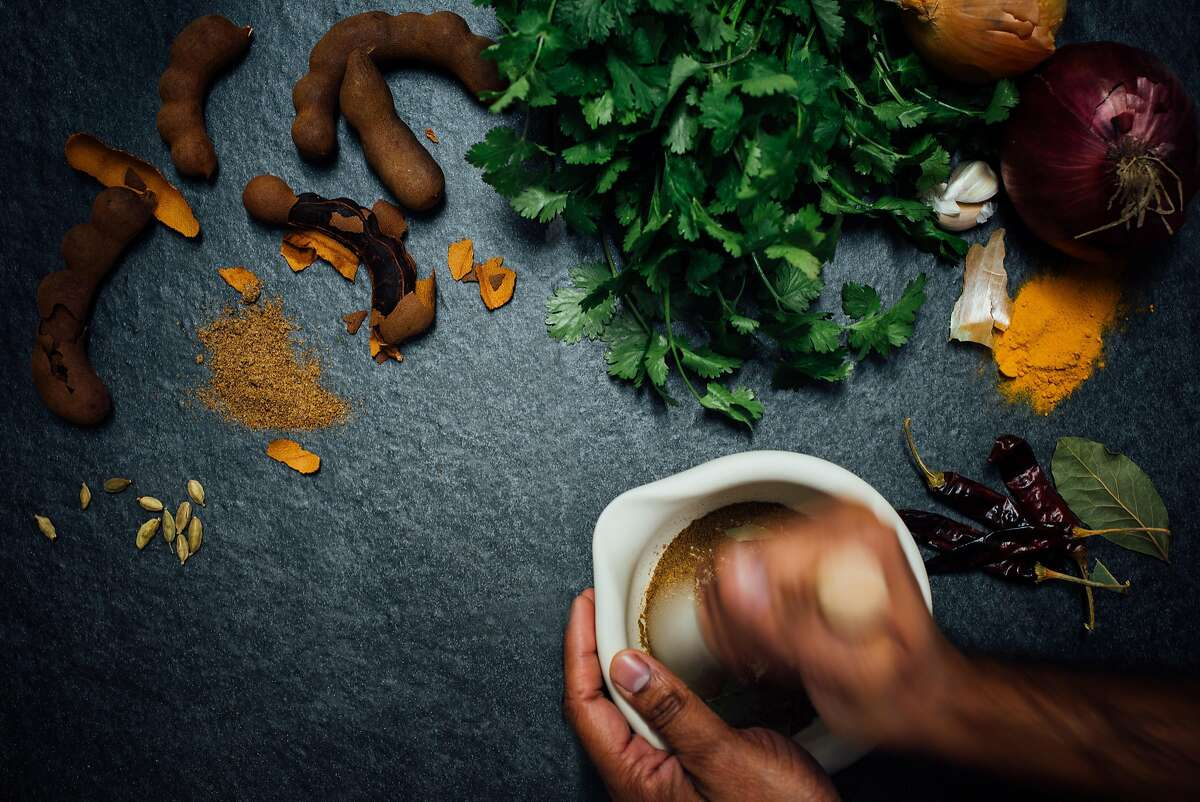 Items for an Indian pantry, including tamarind pods (left),cilantro, dried chiles and a mortar and pestle for grinding.