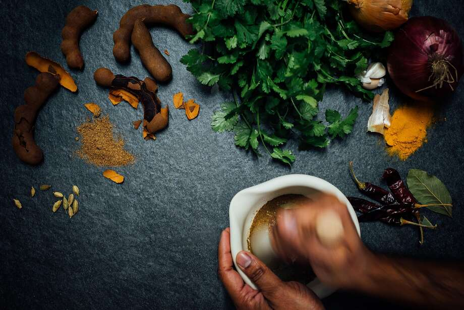 Items for an Indian pantry, including tamarind pods (left),cilantro, dried chiles and a mortar and pestle for grinding. Photo: Nik Sharma