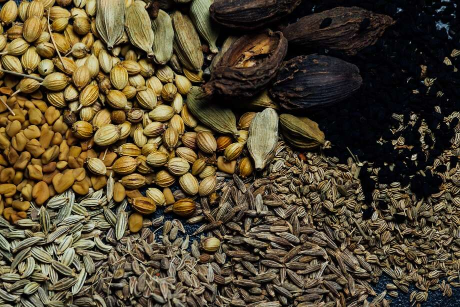 A collection of whole spices, including coriander (clockwise from top left), green cardamom, black cardamom, nigella, anise, cumin, caraway, fennel and fenugreek. Photo: Nik Sharma