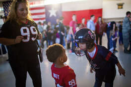 Roy Montiel, right, 8, plays with his brother Jayden Harrell, 3, while their mother Aracely Harrerll, left, watches while waiting in line to meet football players at the Super Bowl LI Salute to Service Barbeque at the Ellington Field Joint Base Reserve, Tuesday, Jan. 31, 2017, in Houston. ( Marie D. De Jesus / Houston Chronicle )