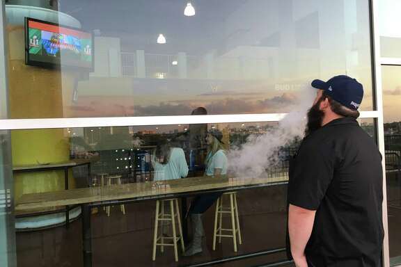 Chad Wixon exhales banana-and-peanut-butter vapor and watches the Atlanta Falcons and New England Patriots play in Super Bowl LI through a glass window. Fans in NRG Stadium's designated smoking area were sequestered from quality views of the game.
