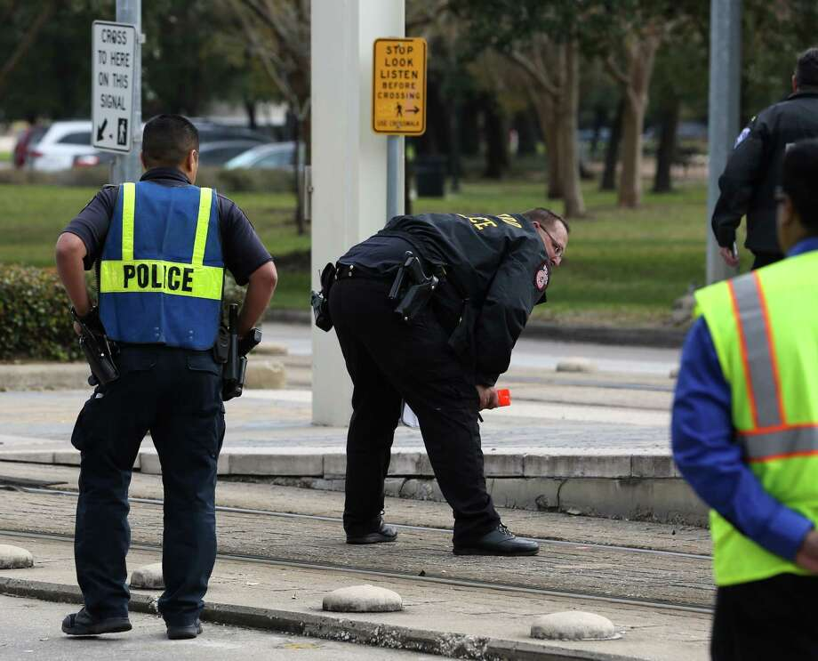 A METRO Police Department officer looks at the light rail tracks before making marks for during the investigation of a METRO Rail hit and killed a female bicyclist at the crosswalk of Fannin Street and Sunset Boulevard next to Hermann Park on Friday, February 3, in Houston. ( Yi-Chin Lee/ Houston Chronicle) Photo: Yi-Chin Lee / Houston Chronicle, METROL Rail / Houston Chronicle 2017