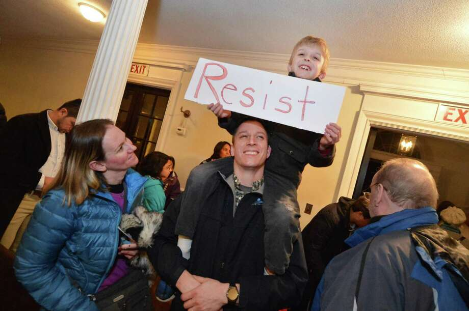 "Ten-year-old Daniel Silvester sits on his father Jay's shoulders, with mom, Amy, and holds a ""Resist"" sign for everyone to read as they leave an Interfaith service to stand with the community's Muslim brothers and sisters at the First Congregational Church in Norwalk on Monday. Photo: Alex Von Kleydorff / Hearst Connecticut Media / Connecticut Post"