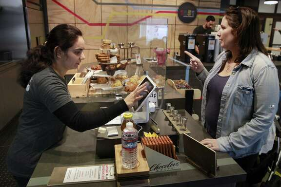 Nazira Babori (left), a refugee from Afghanistan, takes Sarah Gregson's order Friday at 1951 Coffee Company. Babori recently fled Kabul, where she worked with the United Nations.