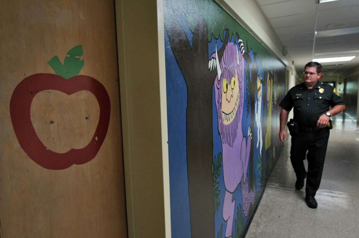 Albany County Sheriff's Office Inspector Mark DeFrancesco walks past a mural inspired by the children's book,
