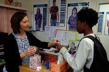 Nurse Sherri Allen hands a cough drop to freshman Kash Hageon at Kountze High School on Monday. The flu has been making the rounds in Kountze and other schools.  Photo taken Monday 2/6/17 Ryan Pelham/The Enterprise