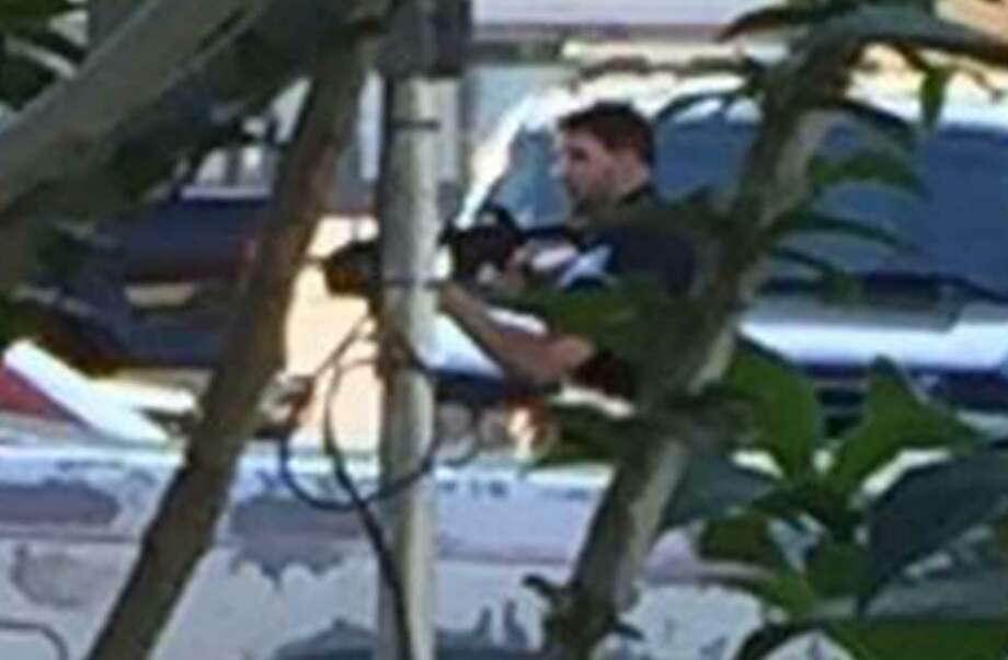 Enlargement of the previous photo showing Beaumont Police officer Chase Welch carrying a rifle toward Herby Balance's home during a March incident where Welch shot and killed Ballance. The photo was taken by a Ballance family member from behind a bush.  Photo provided by Richard Waits