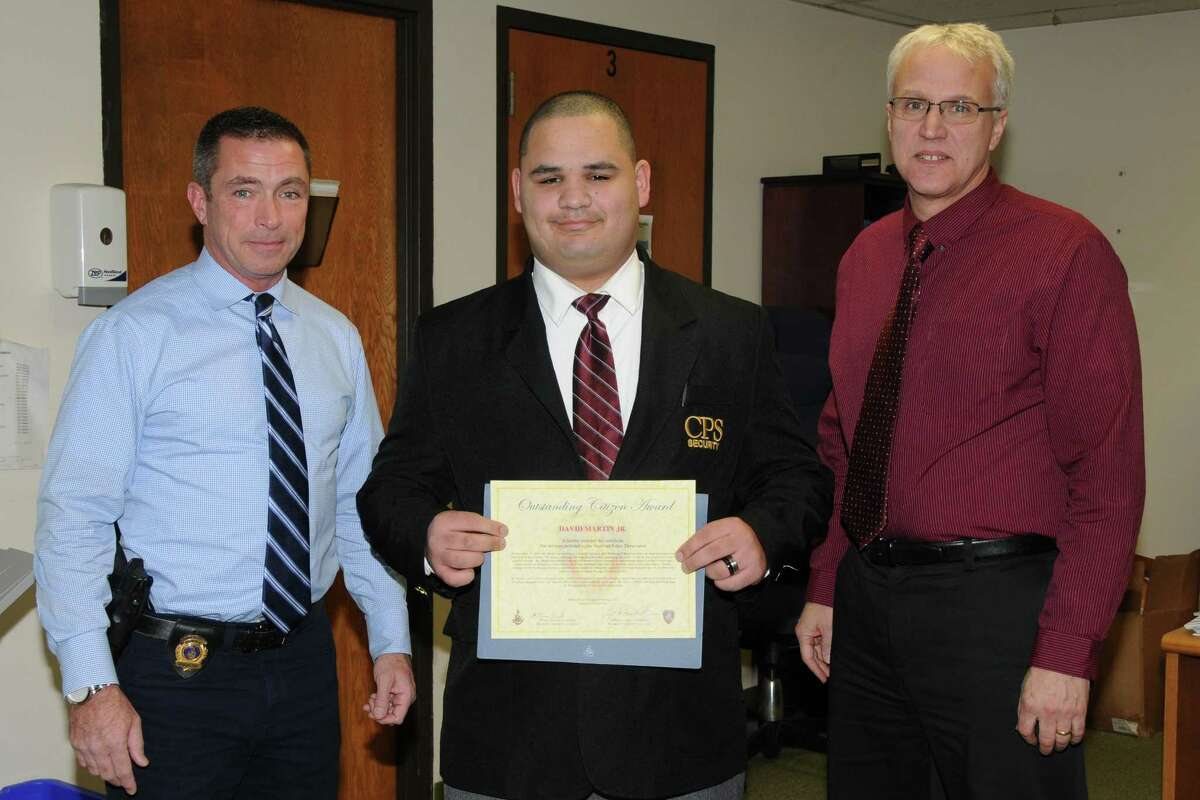 Security guard David Martin, flanked by assistant police chiefs James Matheny (left) and Tom Wuennemann as Martin was given Stamford's Outstanding Citizens Award by the police comission.