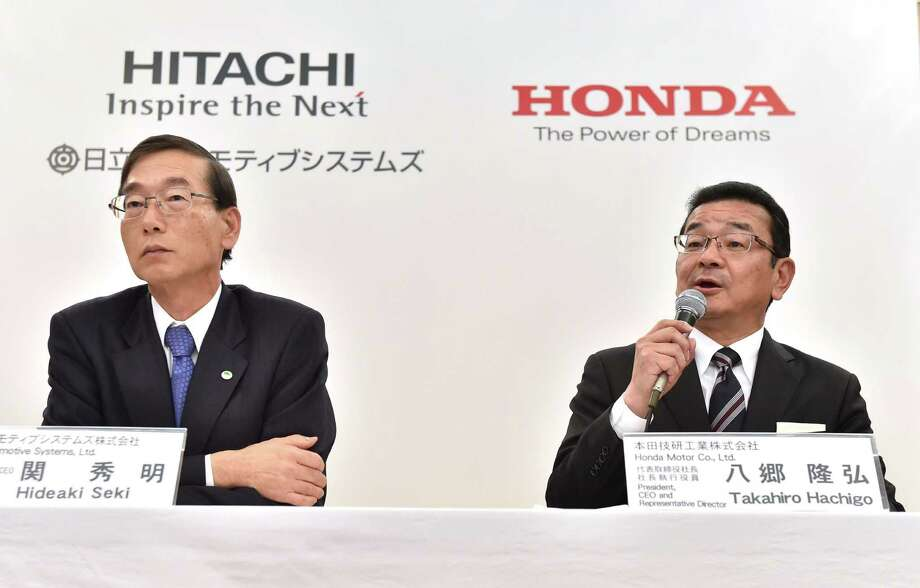 Honda CEO Takahiro Hachigo (right) answers questions as Hitachi Automotive CEO Hideaki Seki listens during their joint news conference Tuesday in Tokyo. Japanese automaker Honda announced a joint venture with Hitachi Automotive to collaborate in the field of electric and hybrid vehicles. Photo: Kazuhiro Nogi /AFP /Getty Images / AFP or licensors
