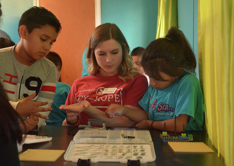Genna Peard, center, Cy-Hope Center Director, helps Team Daniel, left, and Diana, right, work on their pirate ship using LEGO Robotics during their Bricks4Kidz class at the Longhorn Cy-Hope trailer in Cypress on Feb. 3, 2017. (Photo by Jerry Baker/Freelance) Photo: Jerry Baker, Freelance / Freelance