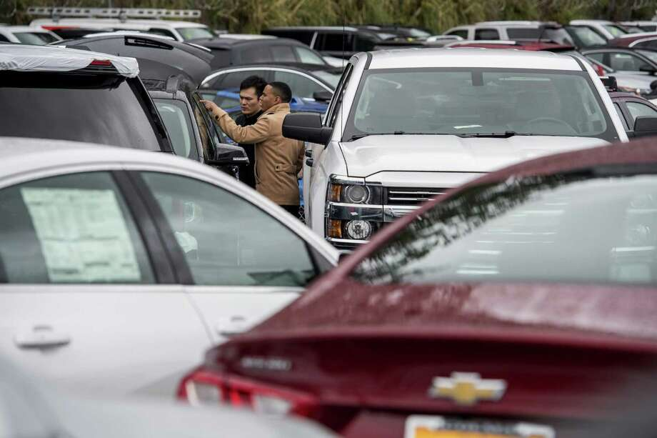 A salesman (right) helps a potential customer inspect a General Motors SUV at a California dealership. GM reported full-year net income of $9.4 billion, but an encore could be a lot harder. Overall auto sales are flattening in the U.S., GM's biggest profit center, and car inventories are growing. Economic troubles linger in Europe and South America. And a new U.S. president wants to redo the North American Free Trade Agreement and could slap a border tax on imports from Mexico. Photo: David Paul Morris /Bloomberg News / © 2017 Bloomberg Finance LP