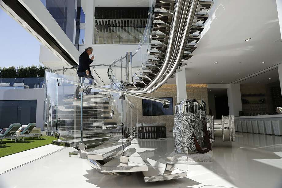 Developer Bruce Makowsky walks up the handcrafted steel staircase next to a large sculpture of a Leica camera at a $250 million mansion he built in the Bel Air area of Los Angeles. Photo: Jae C. Hong, Associated Press