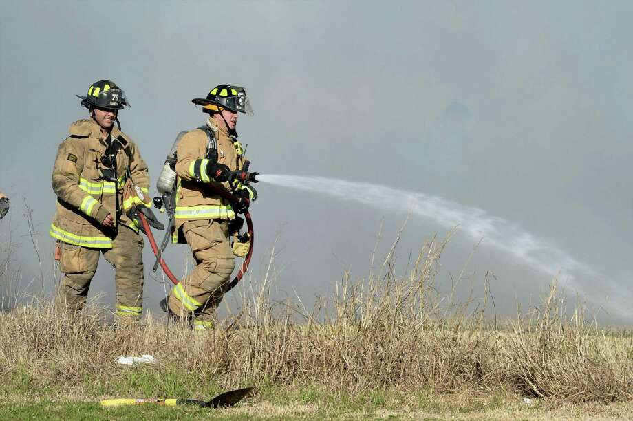 Houston Fire Department crews work to extinguish a large grass fire at the southeast corner of Bellaire Blvd. and Howell Sugar Land Rd., Houston, TX on January 30, 2017 Photo: Craig Moseley, Staff / ©2017 Houston Chronicle