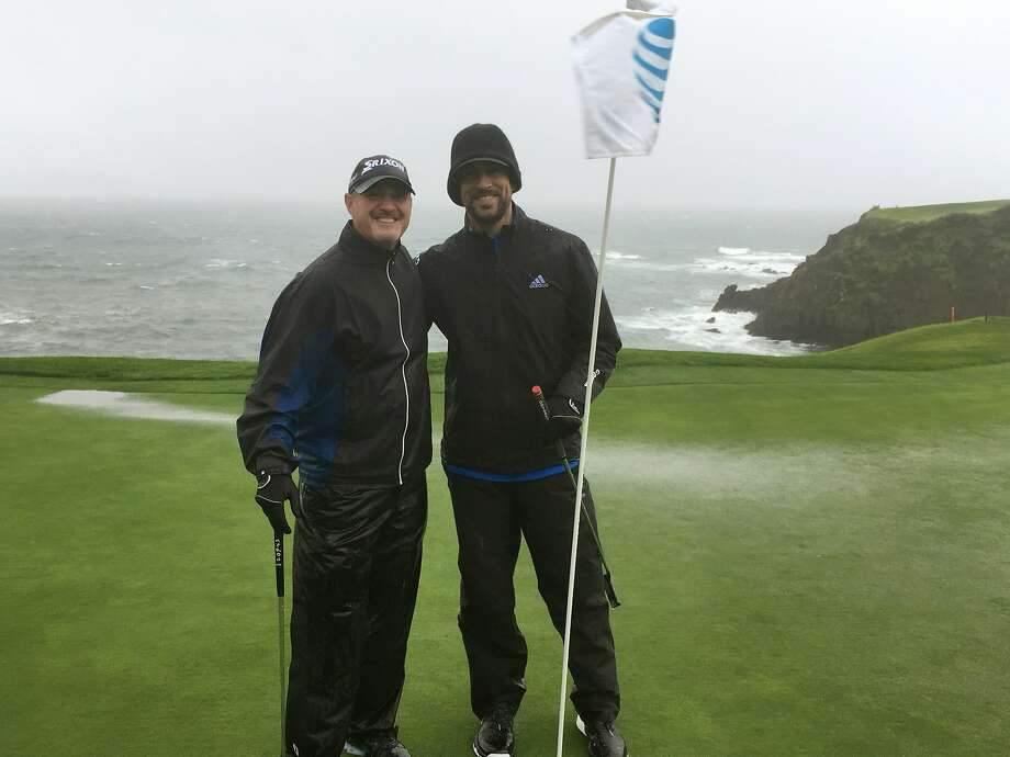 PGA Tour veteran Jerry Kelly, left, and Green Bay quarterback Aaron Rodgers pose on the 8th green at Pebble Beach, Calif., on Tuesday, Feb. 7, 2017, while playing in  40 mph wind and rain. Only at Pebble Beach are players willing to go out in such miserable conditions.  (AP Photo/Doug Ferguson) Photo: Doug Ferguson, Associated Press