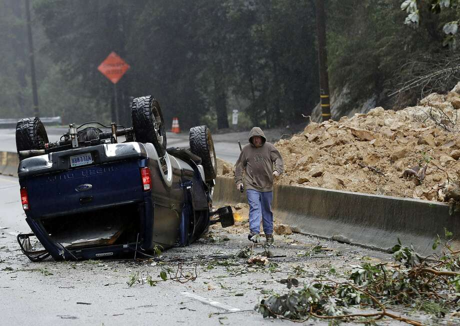 A tow truck operator walks past an overturned vehicle on the south bound lane next to a mudslide which caused the complete closure of Highway 17 north Tuesday, Feb. 7, 2017, south of Santa Cruz, Calif. Flash flood watches are in place for parts of Northern California down through the Central Coast as heavy rains swamp roads and threaten to overtop rivers and creeks. Photo: Marcio Jose Sanchez, Associated Press