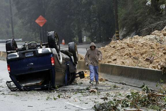 A tow truck operator walks past an overturned vehicle on the south bound lane next to a mudslide which caused the complete closure of Highway 17 north Tuesday, Feb. 7, 2017, south of Santa Cruz, Calif. Flash flood watches are in place for parts of Northern California down through the Central Coast as heavy rains swamp roads and threaten to overtop rivers and creeks. (AP Photo/Marcio Jose Sanchez)