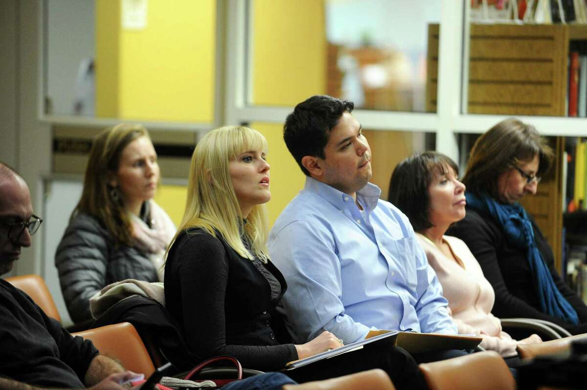 Springdale residents Svitlana Pasquale, center left, and Cristian Cano listen to a community forum regarding excessive noise from train horns and whistles inside the Harry Bennett Library auditorium in Stamford, Conn. on Monday, Feb. 6, 2017.