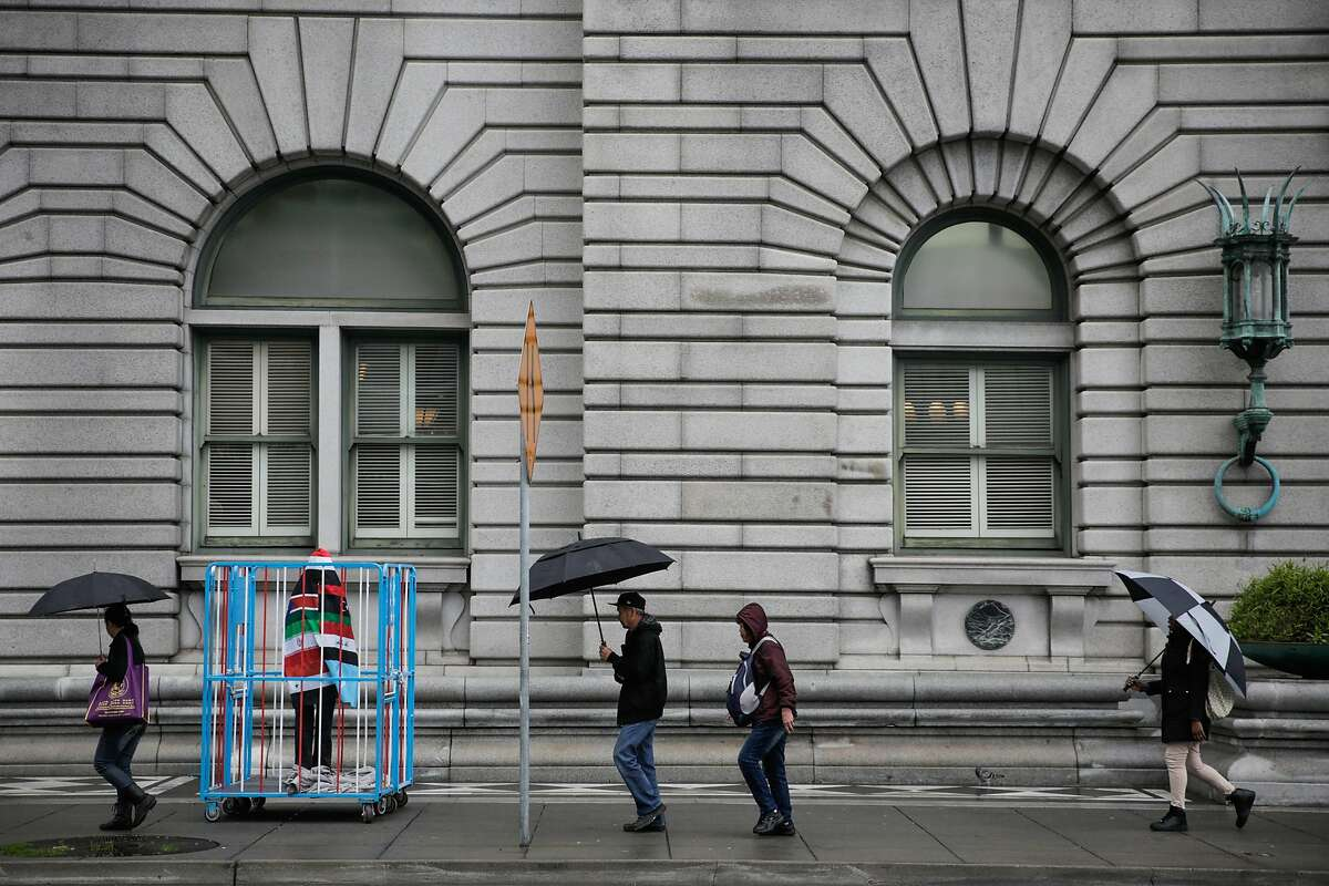 People carry umbrellas as they walk in the rain past an art piece outside of the Ninth Circuit Court of Appeals which will be hearing the travel ban case this afternoon, in San Francisco, California, on Tuesday, Feb. 7, 2017. The art piece is a caged figure covered in the seven flags of the countries that are currently being banned from entering the United States. The artist (who wished to remain anonymous) said he made the piece from