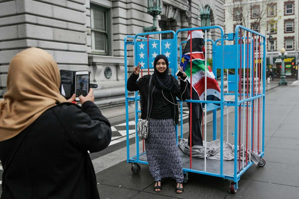 Kawkap Alawdi, 34 (left) photographs her niece Baraah Alawdi, 19 (right), who are originally from Yemen, in front of an art piece referencing President Donald Trump's travel ban outside the Ninth Circuit Court of Appeals which will be hearing the travel ban case this afternoon, in San Francisco, California, on Tuesday, Feb. 7, 2017. The art piece is a caged figure covered in the seven flags of the countries that are currently being banned from entering the United States. The artist (who wished to remain anonymous) said he made the piece from