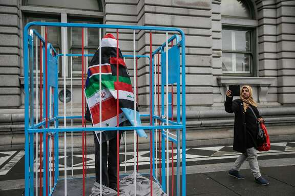 "Kawkap Alawdi, 34 (right) who is originally from Yemen, photographed an art piece referencing President Donald Trump's travel ban, outside the Ninth Circuit Court of Appeals which will be hearing the travel ban case this afternoon, in San Francisco, California, on Tuesday, Feb. 7, 2017. The art piece is a caged figure covered in the seven flags of the countries that are currently being banned from entering the United States. The artist (who wished to remain anonymous) said he made the piece from ""found objects""."