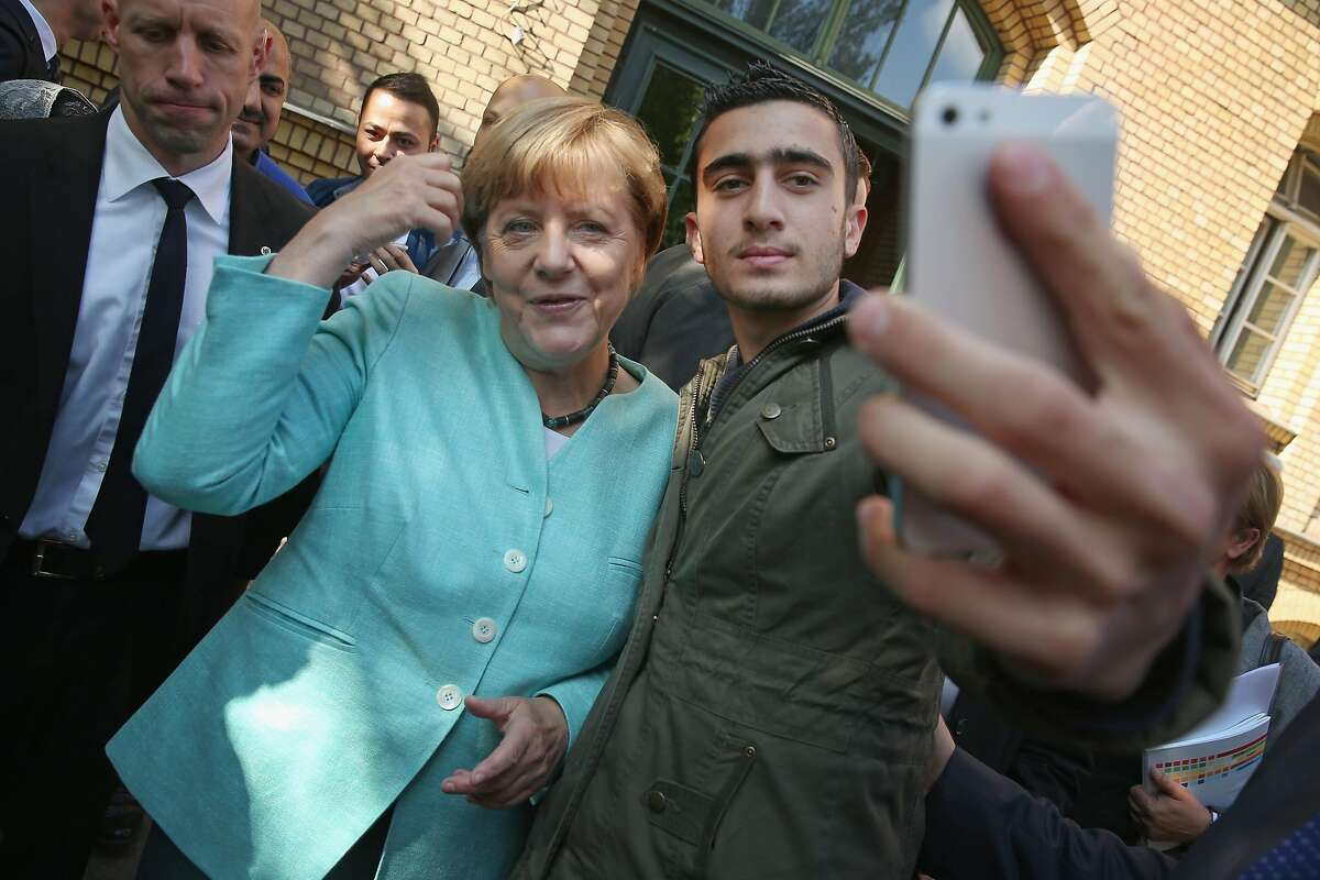 Anas Modamani, a Syrian refugee, takes a picture with German Chancellor Angela Merkel in 2015.