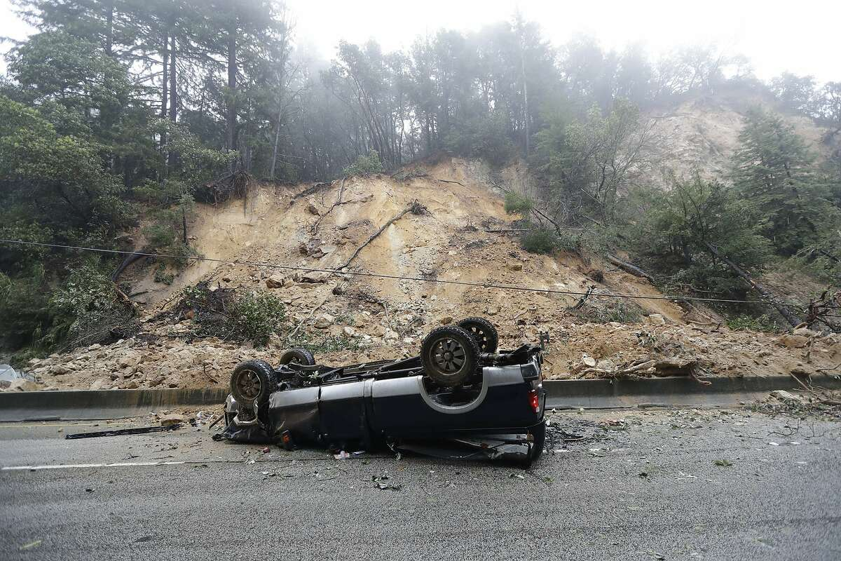 An overturned vehicle blocks a south bound lane next to a mudslide on Highway 17 Tuesday, Feb. 7, 2017, south of Santa Cruz, Calif. Flash flood watches are in place for parts of Northern California down through the Central Coast as heavy rains swamp roads and threaten to overtop rivers and creeks. (AP Photo/Marcio Jose Sanchez)