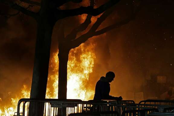 FILE - In this Feb. 1, 2017 file photo, a fire set by demonstrators protesting a scheduled speaking appearance by Breitbart News editor Milo Yiannopoulos burns on Sproul Plaza on the University of California, Berkeley campus. UC Berkeley police took a hands-off approach to protesters on the campus last week when violent rioters overtook a largely peaceful protest against a controversial speaker. But that response is being questioned as demonstrators become increasingly hostile and politics are more polarized. (AP Photo/Ben Margot, File)