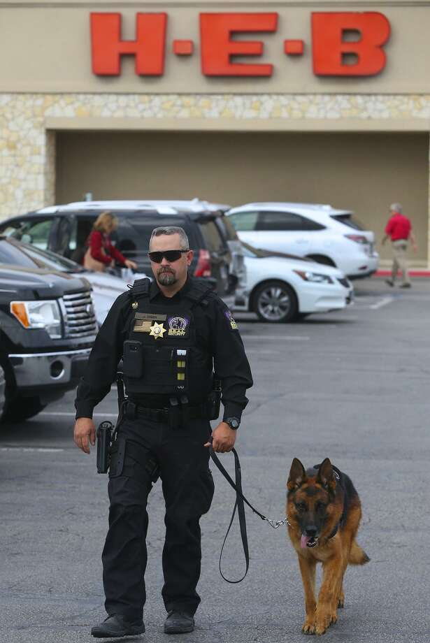 """Security officer Justin Owen patrols Monday February 6, 2017 at the H-E-B Lincoln Heights store with a S.E.A.L. Security canine officer """"Fak"""" (right). H-E-B is bringing canine security officers to seven stores in the San Antonio area as part of a partnership with Houston-based S.E.A.L. Security Solutions. Photo: John Davenport /San Antonio Express-News / ©San Antonio Express-News/John Davenport"""