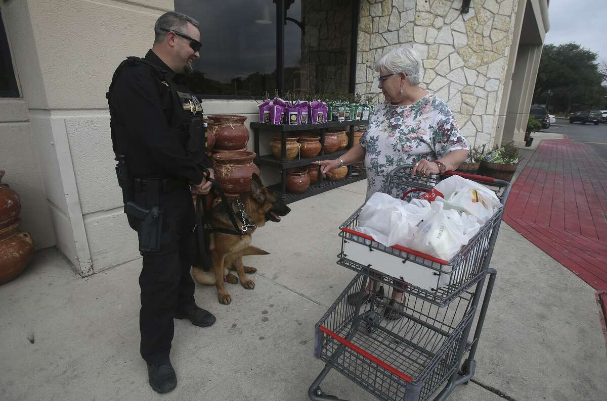 Security officer Justin Owen (left) speaks Monday February 6, 2017 with H-E-B customer Jean Vargo (right) as Owen stands guard in front of the Lincoln Heights H-E-B store with S.E.A.L. Security canine officer