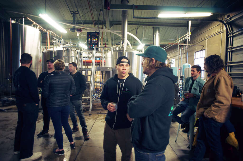 Brewers chat and sip beer at Fort Point's brewery on brew day.
