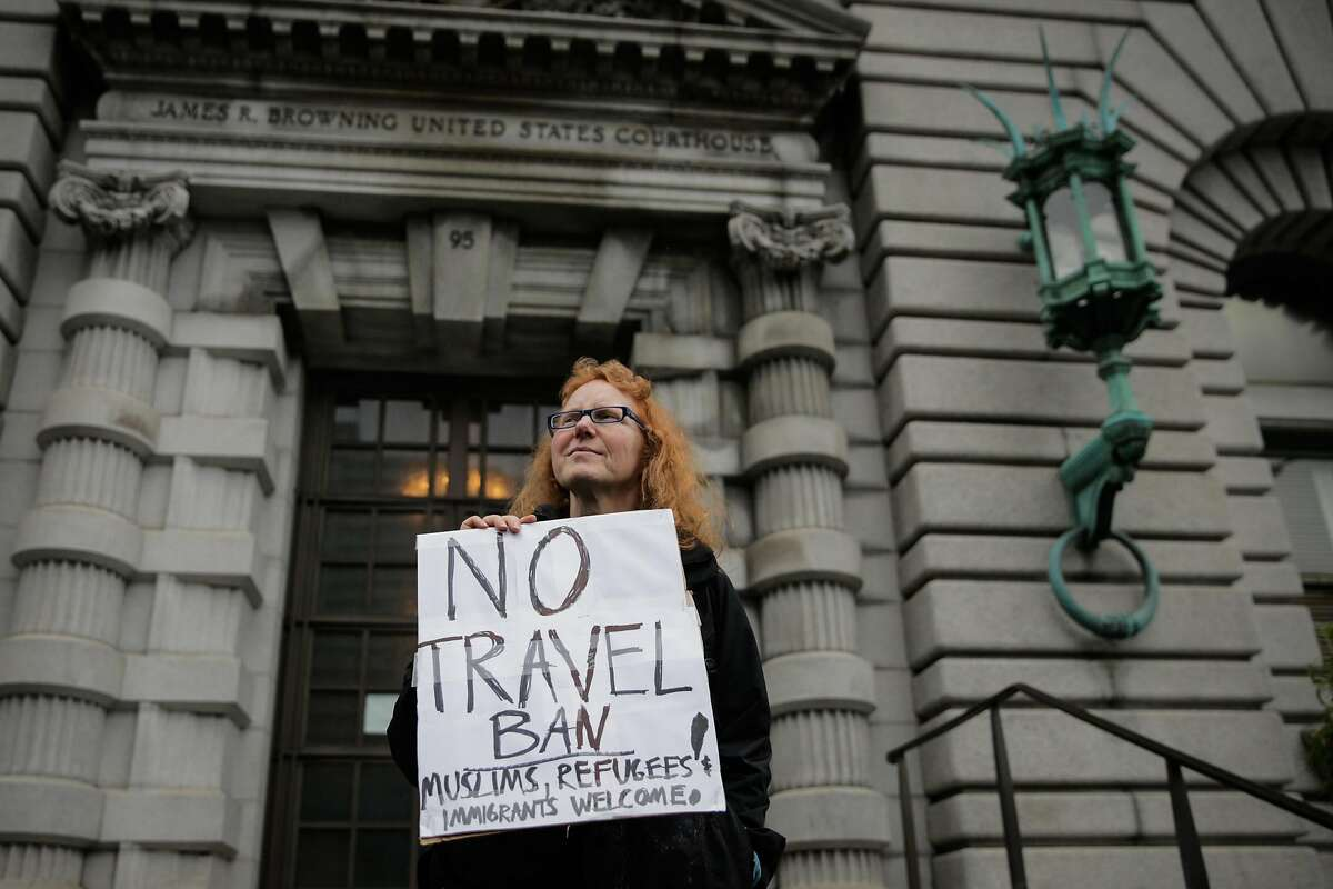 Demonstrator Beth Kohn (center) protests President Donald Trump's travel ban while standing in front of the Ninth Circuit Court of Appeals which is hearing the travel ban case today in San Francisco, California, on Tuesday, Feb. 7, 2017.