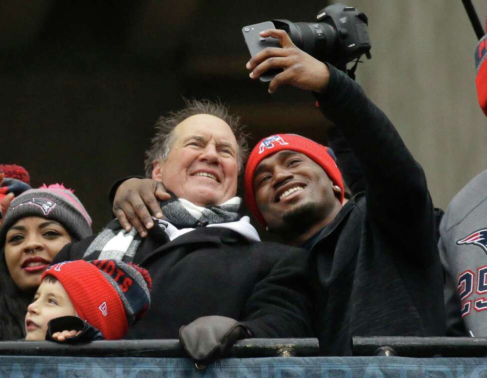 New England Patriots running back Dion Lewis takes a selfie with head coach Bill Belichick during a rally Tuesday, Feb. 7, 2017, in Boston, to celebrate Sunday's 34-28 win over the Atlanta Falcons in the NFL Super Bowl 51 football game in Houston. (AP Photo/Elise Amendola) ORG XMIT: MAEA103