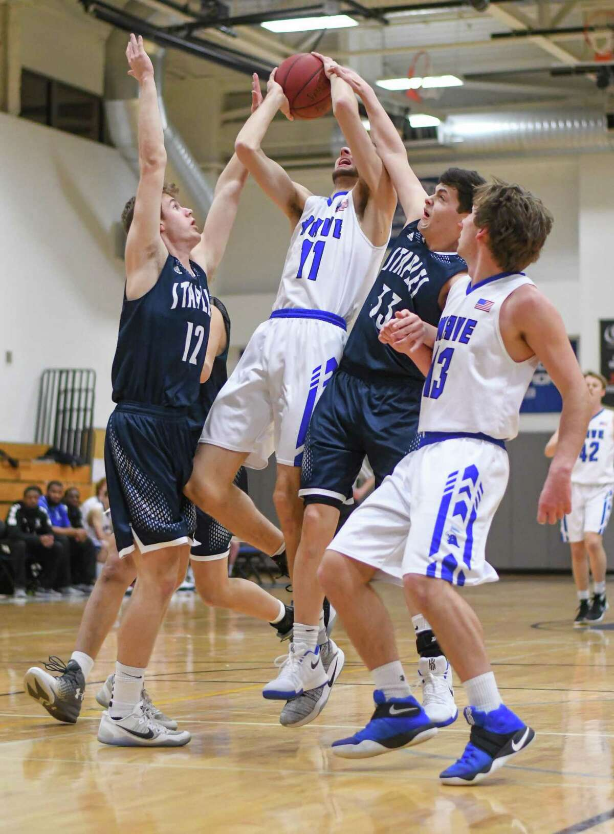 Darien's Alex Preston (11) is fouled by Staples on Tuesday night.