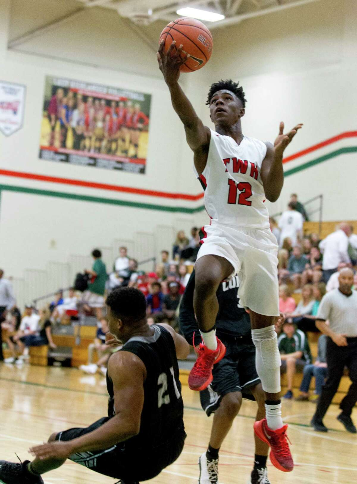 The Woodlands guard Kesean Carter (12) makes a layup past Conroe center Lavery Sheperd (21) during the first quarter of a District 12-6A high school boys basketball game at The Woodlands High School Tuesday, Feb. 7, 2017, in The Woodlands. The Woodlandsdefeated Conroe 72-52.