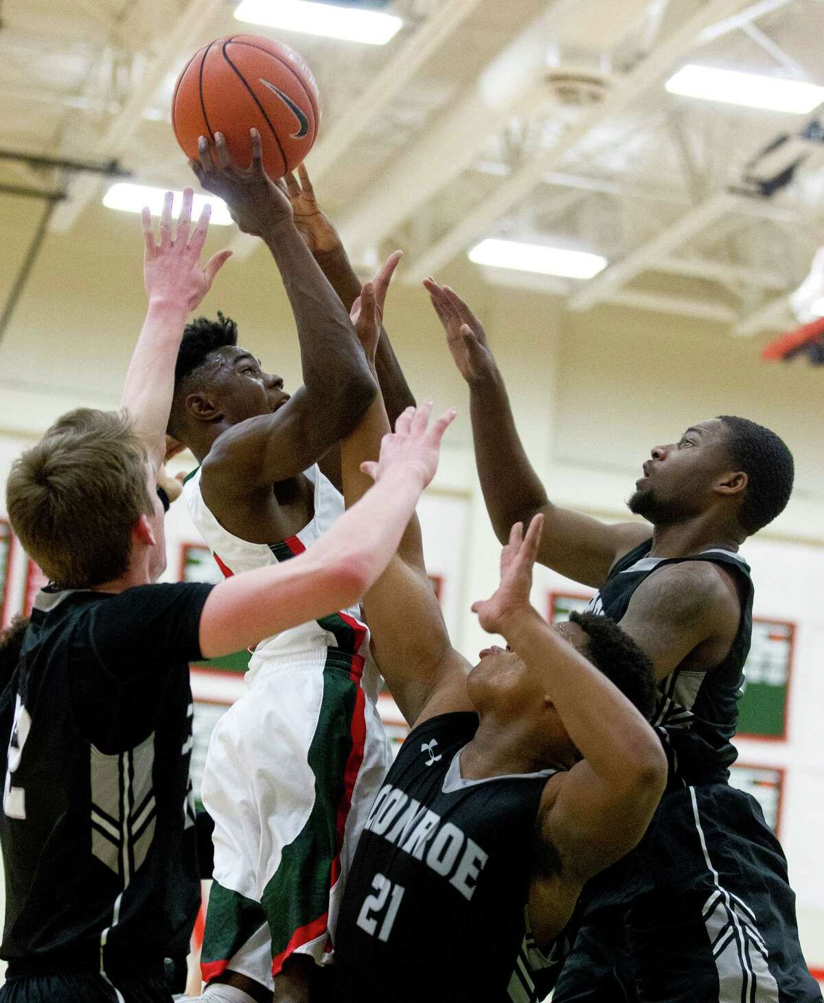 The Woodlandsguard Kesean Carter (12) shoots under pressure from Conroe center Lavery Sheperd (21), guard Blain Alger (22) and forward Quentin Brown (12) during the first quarter of a District 12-6A high school boys basketball game at The Woodlands High School Tuesday, Feb. 7, 2017, in The Woodlands. The Woodlandsdefeated Conroe 72-52.