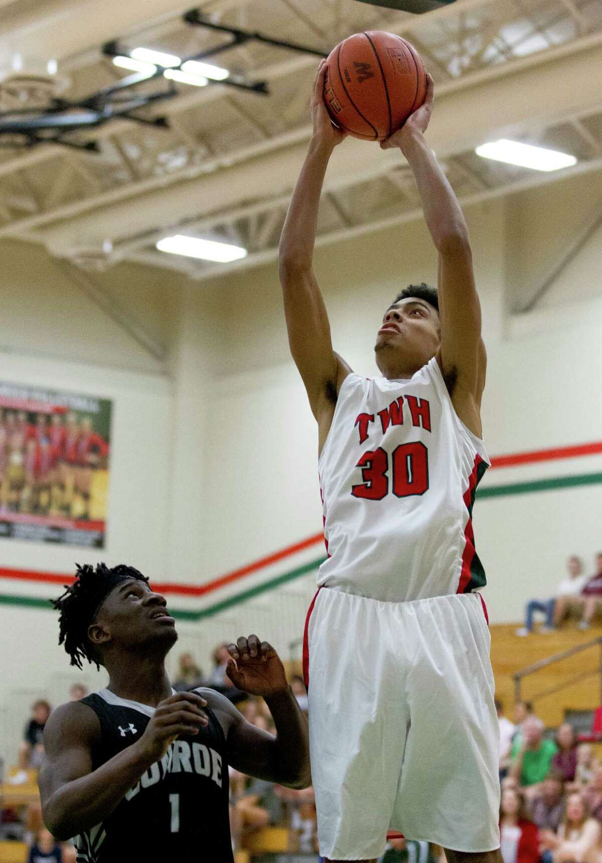 The Woodlands guard Sammy Williams (30) shoots over Conroe guard Jay Lewis (1) during the first quarter of a District 12-6A high school boys basketball game at The Woodlands High School Tuesday, Feb. 7, 2017, in The Woodlands. The Woodlandsdefeated Conroe 72-52.