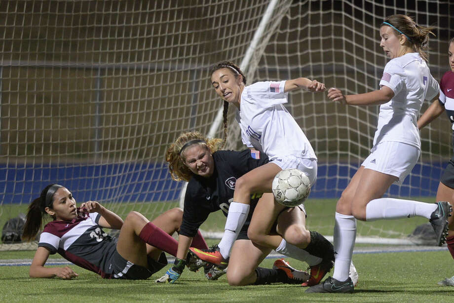 Midland High's Kylie VonHolle (right) scores as teammate Ashlynn Dominguez (20) gets tangled up with Lee goalkeeper Jenna McEnaney (00) Tuesday, Feb. 7, 2017, at Grande Communications Stadium. James Durbin/Reporter-Telegram Photo: James Durbin