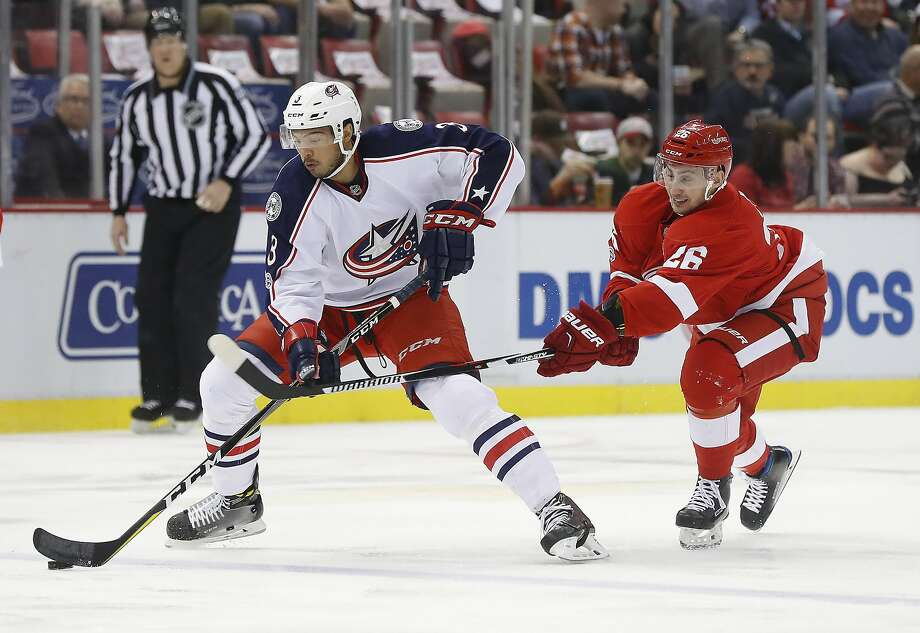 Columbus defenseman Seth Jones (left) protects the puck from Detroit right wing Tomas Jurco during the first period. Photo: Paul Sancya, Associated Press
