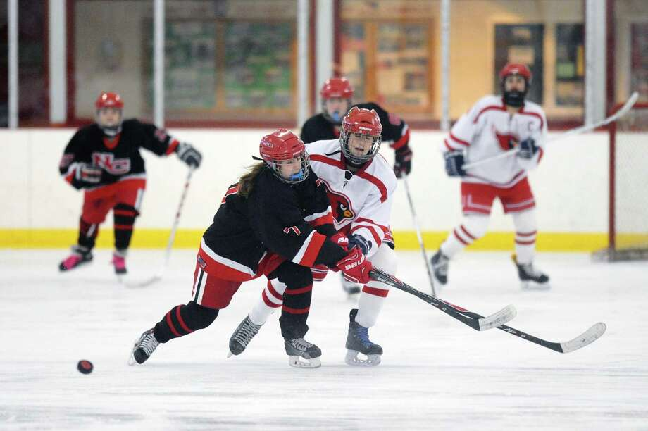 New Canaan sophomore Jessie Eccleston, center left, and Greenwich sophomore Grace Fahey jockey for the puck during a girls varsity hockey game at Dorothy Hamill Skating Rink in Greenwich on Monday. The teams tied at 2-2. Photo: Michael Cummo / Hearst Connecticut Media / Stamford Advocate