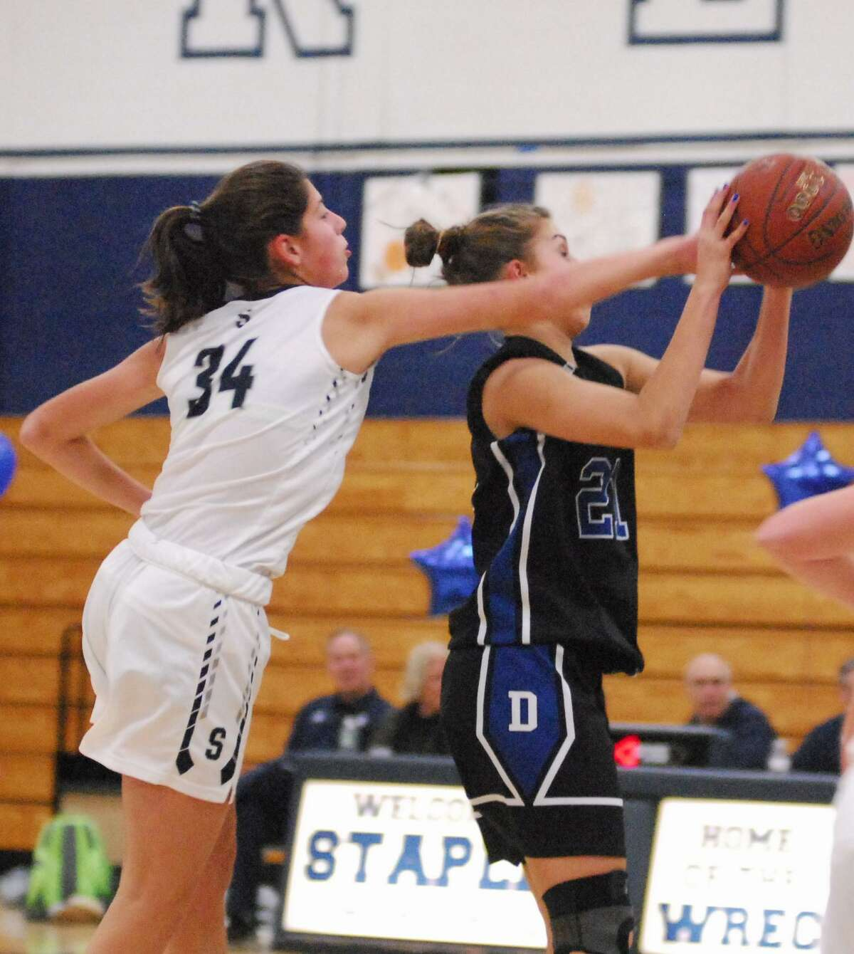 Darien's Christine Fiore, right, catches the ball while Staples' Arianna Gerig defends during a game on Tuesday. Fiore scored 28 points as the Blue Wave won 63-52.